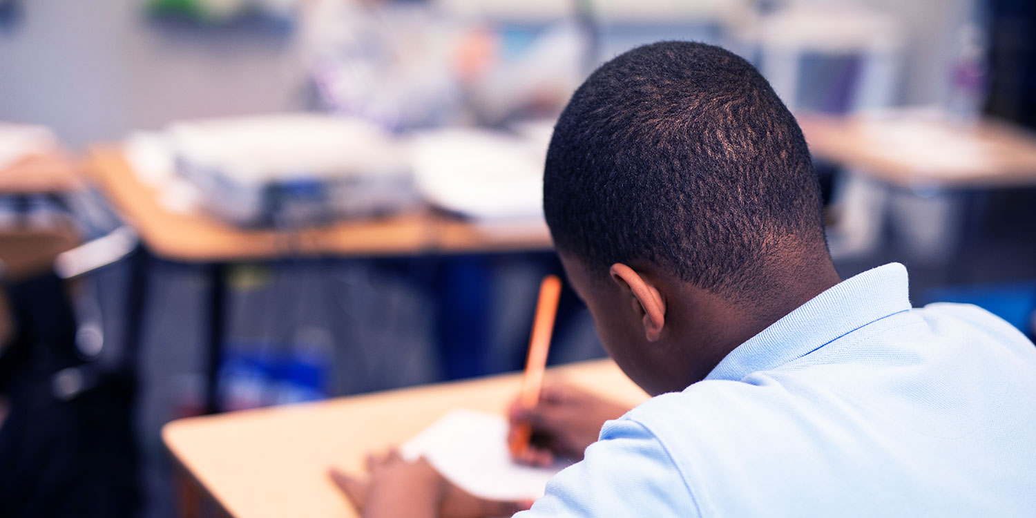 Middle school student completing classwork at their desk.
