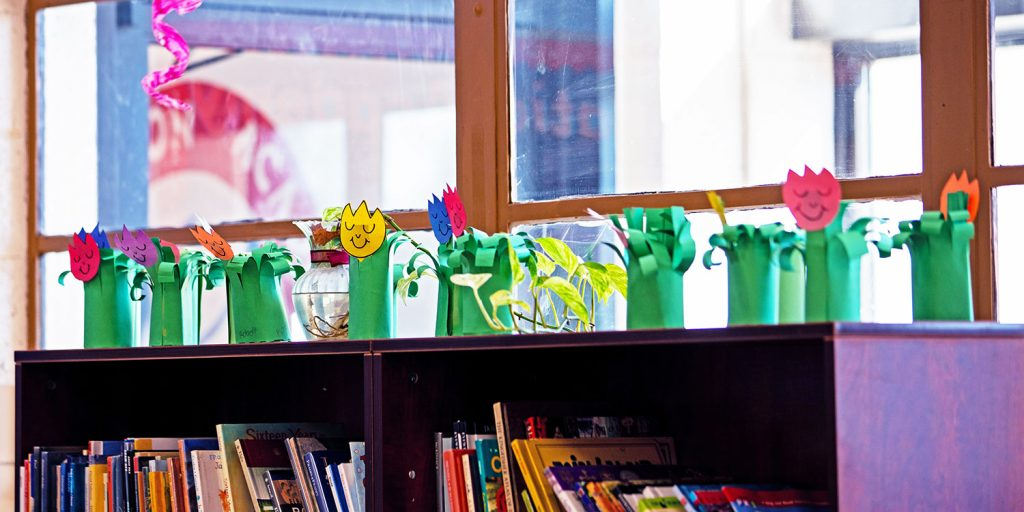Flower art projects displayed on a bookshelf by a window.