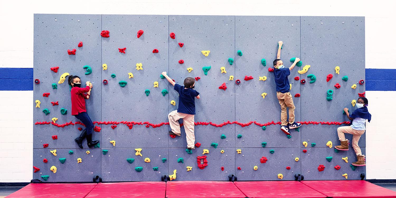 Students traversing the indoor climbing wall.